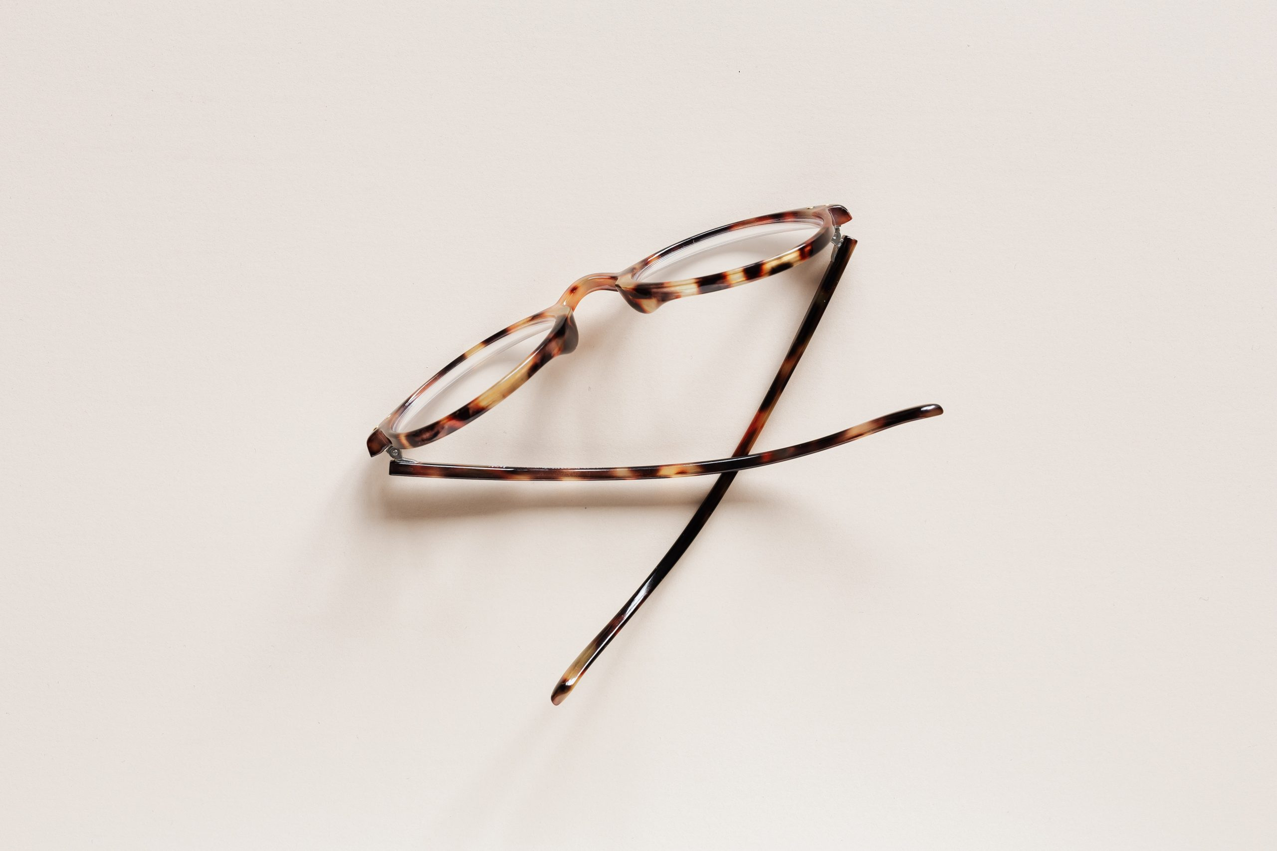 stylish-eyeglasses-placed-on-beige-surface-4226877